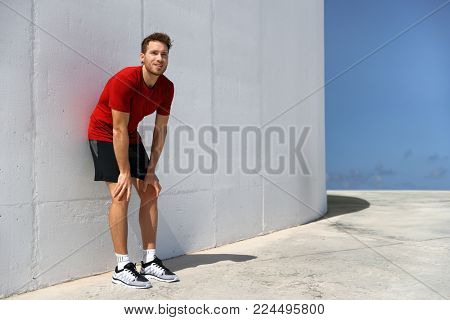 Tired male athlete runner exhausted of cardio workout breathing hard after difficult exercise. Fitness man running sweating of heat exhaustion leaning on wall of muscle back pain or cramps.
