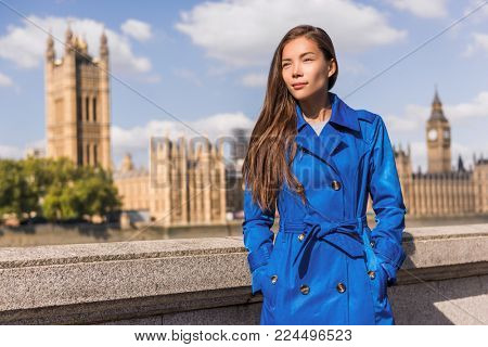 London city lifestyle Asian businesswoman Europe autumn travel in blue trench coat. Multiracial model in fashion fall outerwear at Westminster and Big Ben, famous european urban destination.