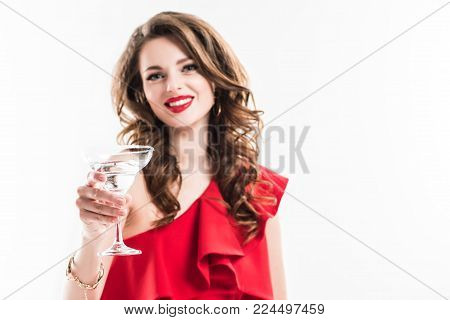 fashionable girl in red dress showing glass of cocktail isolated on white