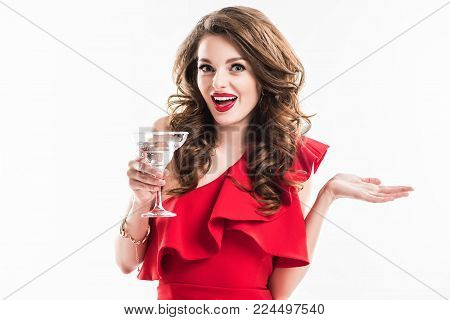 surprised fashionable girl in red dress holding glass of cocktail isolated on white