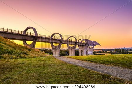 Falkirk Wheel at sunset. Falkirk Wheel is a rotating boat lift in Scotland and connects the Forth and Clyde Canal with the Union Canal.