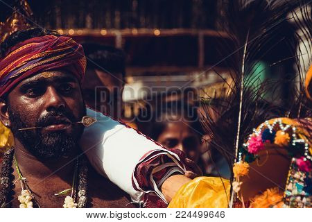 BATU CAVES, SELANGOR, MALAYSIA - 31 JANUARY 2018 Hindu devotees celebrate Thaipusam festival with procession and offerings. People portrait. Religion concept. Culture and traditions. Pierced tongue