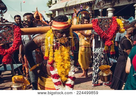 BATU CAVES, SELANGOR, MALAYSIA - 31 JANUARY 2018 Hindu devotees celebrate Thaipusam festival with procession, offerings. Man portrait. Religion concept. Culture and traditions. Asian travel. Garlands