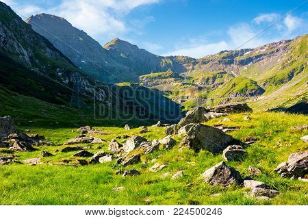 lovely scenery of Transfagarasan road in valley. rocks on grassy meadow and slopes. half of the valley in shade of mountain ridge