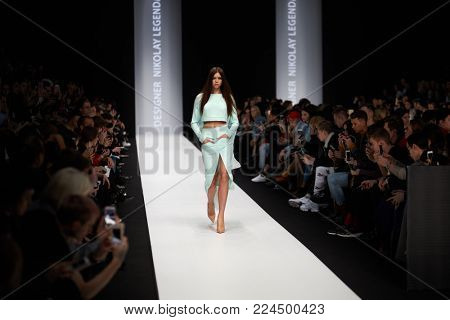 MOSCOW, RUSSIA - OCT 24, 2017: People in auditorium and model on catwalk in Manege during performing designer Nikolay Legenda collection at Mercedes Benz Fashion Week Russia spring-summer 2018.