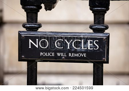 No Cycles restriction sign on railings in Whitehall London UK