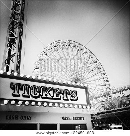 Ticket booth at amusement park with ferris wheel in the background - black and white retro filter