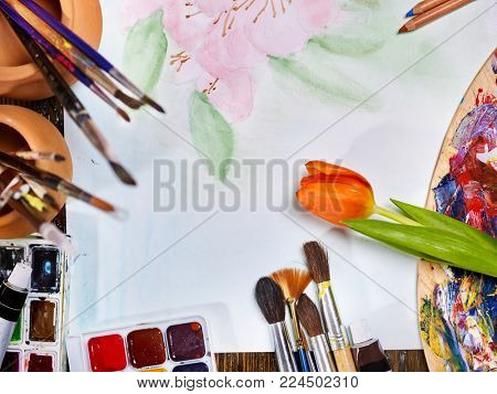 Painting brushes still life on table in art class school. Group of brush in clay jar and palette on wooden table. Flower as symbol of spring discounts. Copy space for text.