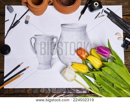 Drawing picture on table in art class school. Group of brush in clay jar on wooden table. Flowers as symbol of spring discounts. Training art graphics courses by nib pen.
