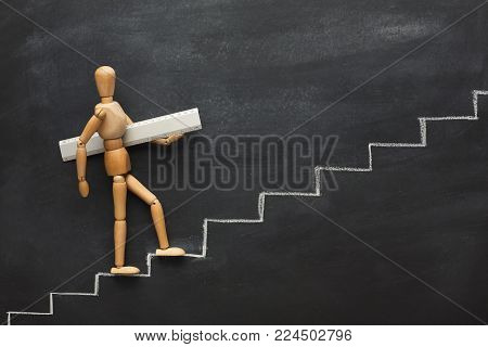 Wooden figure holding ruler and climbing step by step to the top of career and development stairs. Drawn stairs, copy space