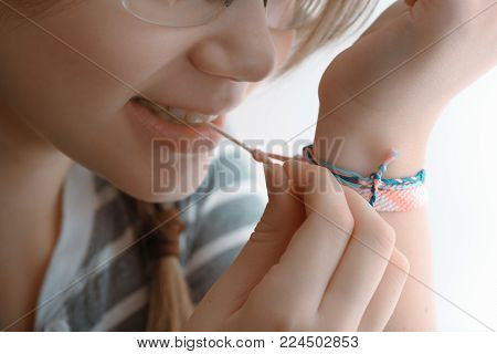 Horizontal shot of a Baby girl with teeth tying the bracelet on her hand