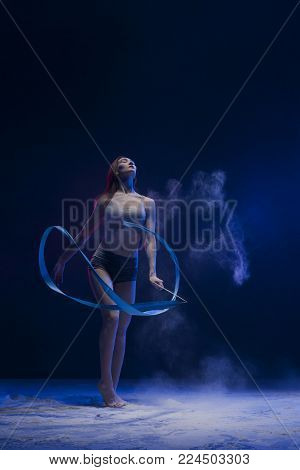 Graceful woman in top and shorts exercising with a gymnastic ribbon in a cloud of dust full-length shot indoors