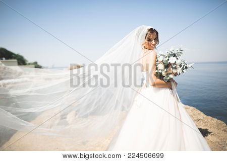 Lovely bride in white wedding dress posing near the sea with beautiful background.