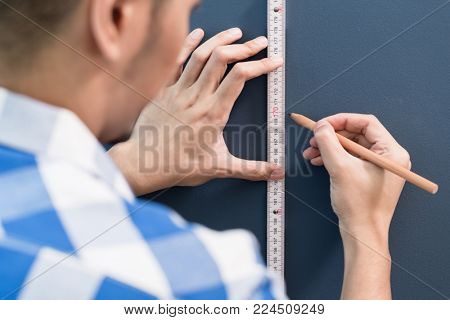 Young Asian handyman sizing with yardstick and pencil