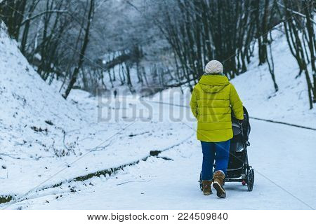 mother walk with baby in baby carriage in winter park