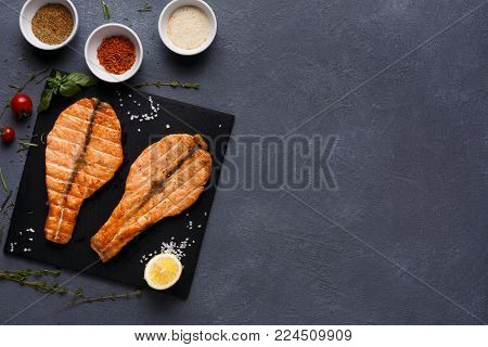 Salmon juicy fillet grilled on barbecue, served with spices assortment. Healthy seafood, red fish steak closeup, restaurant food, mediterranean cuisine concept, top view, copy space