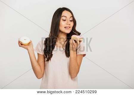 Portrait of a hungry young asian woman eating donuts isolated over white background