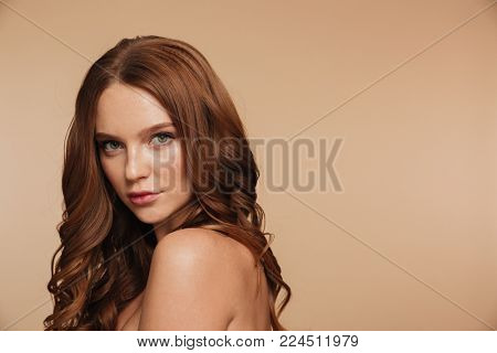 Beauty portrait of mystery ginger woman with long hair posing sideways and looking at the camera over cream background