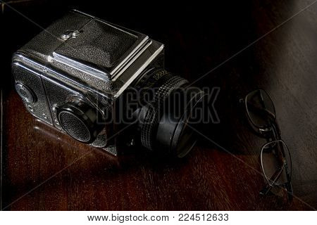 old camera and a pair of specs on a wooden credenza