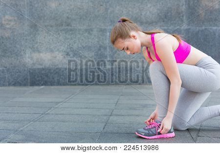 Woman tying shoes laces before running, getting ready for jogging in park, closeup, copy space