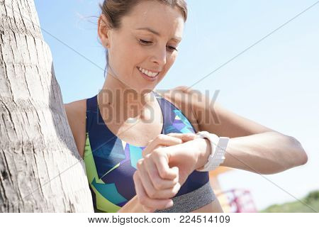 Jogger looking at smartwatch after running