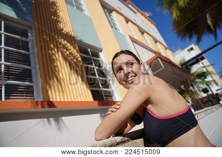 Jogger woman running in the street of sunny city