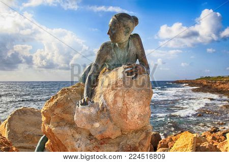PAPHOS, CYPRUS - JANUARY 12, 2018: A bronze statue of woman called 'Sol Alter' by Yiota Ioannidou on a stone located on sea promenade, Paphos, Cyprus.