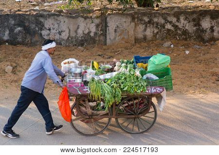 Jaipur, India - 13th Jan 2018: Man selling vegetables by loading them onto a handcart and selling them on the streets of india