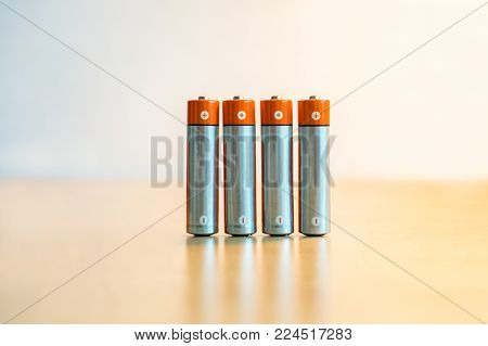 Close-up of four AA batteries standing on a table with plus and minus signs.