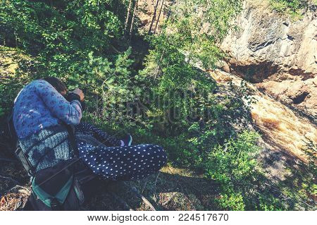 Girl photographs cliffs and turbulent river, Finland. Oulanka National Park