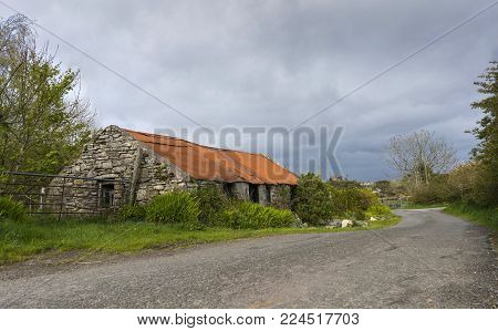 A quaint cottages in Donegal with a rust corrugated roof.
