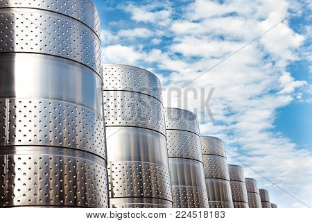 Modern technological industrial equipment of wine factory..Large stainless steel wine distilling tanks on blue cloudy sky background.