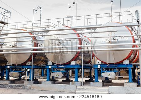 Modern technological industrial equipment of wine factory. Big steel wine distilling tanks.