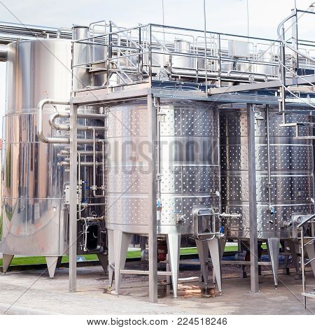 Modern technological industrial equipment of wine factory..Large stainless steel wine distilling vats.