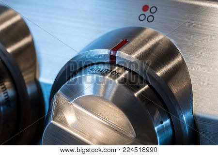 Stainless steel control knob on induction cooktop or hob set to simmer