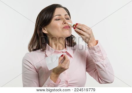 Woman drips drops for nose. White background