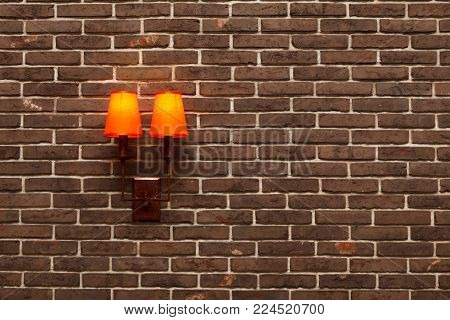 Decorative, neat wall made of brown ceramic bricks and wall lamps with orange shades. Modern imitation of the old brickwork. A fragment of the interior inside the building The background image, texture