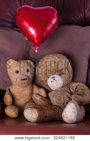 Valentines day image of old aged teddy bear couple holding a red heart balloon. Cute vintage old-aged pensioner toy lovers on their wedding anniversary. Retired but clearly in love.