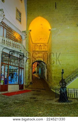 COIMBRA, PORTUGAL - DECEMBER 22, 2017: Evening view of the Almedina arch and tower, in Coimbra, Portugal