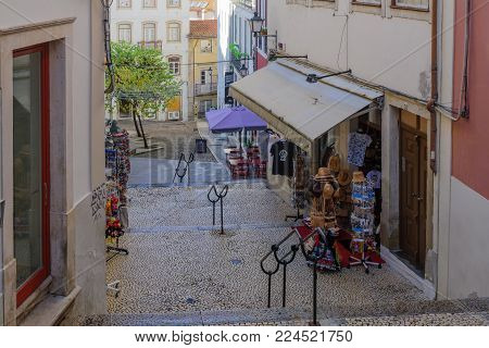 COIMBRA, PORTUGAL - DECEMBER 23, 2017: Old city street with shops, and pedestrians, in Coimbra, Portugal
