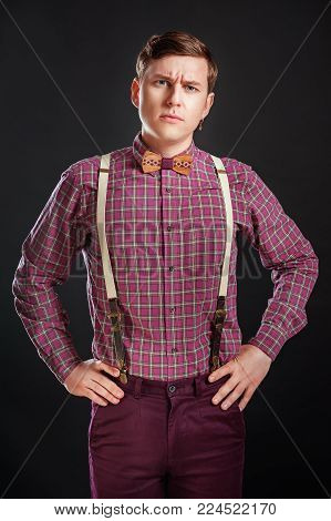 Portrait of young handsome suspicous man in vintage shirt and bow tie with hairstyle keeping hands on hips while standing on black background. Doubt Emotion People Fashion Skeptic concept