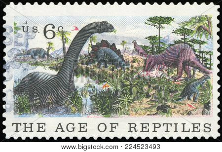 UNITED STATES OF AMERICA - CIRCA 1969: A Stamp printed in USA shows the Brontosaurus, Stegosaurus & Allosaurus, the age of reptiles, circa 1969