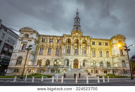 Wide angle bottom view of Bilbao city council at dusk with cloudy sky