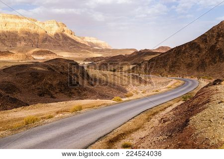 Empty road and curve in dry two-coloured sandstone desert landscape of Timna park near Eilat city, Israel, Near East.
