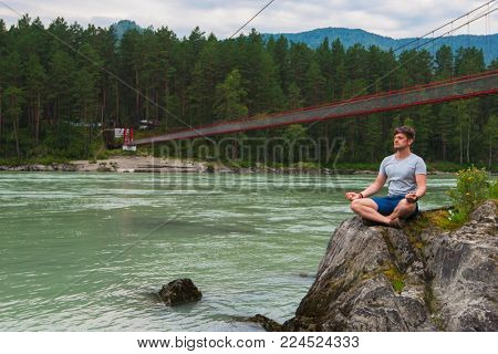 Young man spending time at riverbank of mountain river