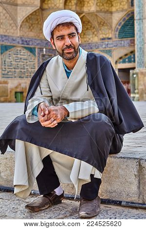 Isfahan, Iran - April 24, 2017: mullah in turban is sitting in the courtyard in Jame prayer hall.