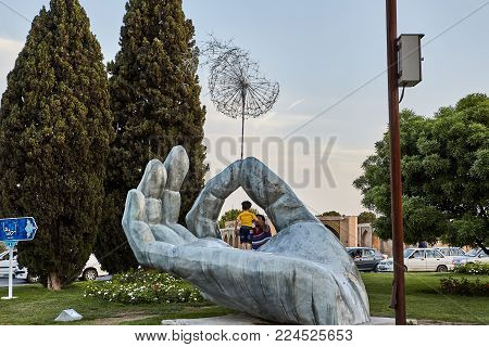 Isfahan, Iran - April 24, 2017: a boy with his father stand on a statue in the form of a large silver palm with a dandelion in the park.