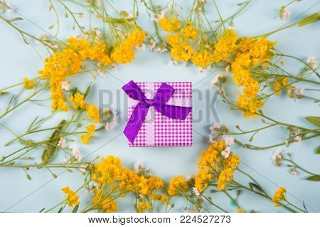 Purple Gift Box Surrounded With Yellow And White Little Flowers On Light Mint Background.