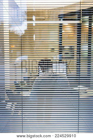 Silhouette of working late businessman man seen through windows blinds working report thesis data analysis bank report view from the street - working late concept business