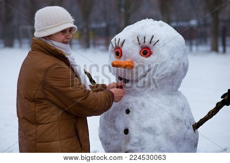 Happy senior woman sculpt and hug a big real snowman in winter park